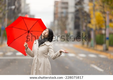 Young Asian woman holding up red umbrella in Autumn city. - stock photo