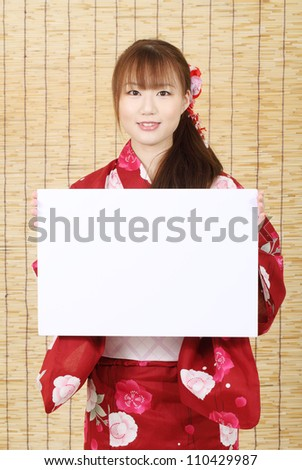 Young asian woman in clothes of kimono holding a blank white board - stock photo