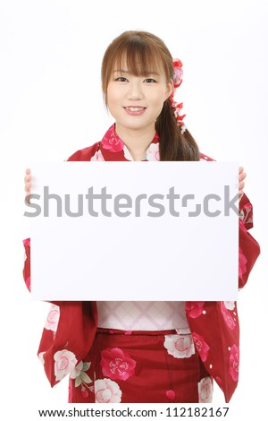 Young asian woman in traditional clothes of kimono holding a blank white board - stock photo
