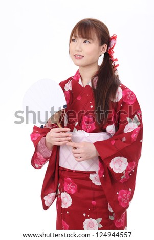 Young asian woman in traditional clothes of kimono with paper fan - stock photo