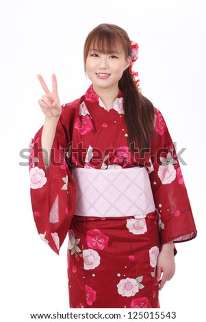 Young asian woman in traditional clothes of kimono with peace sign - stock photo