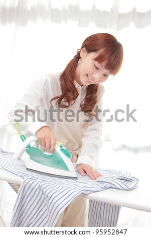 Young Asian woman ironing at the window - stock photo