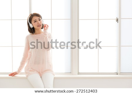 young asian woman listening music in the room - stock photo