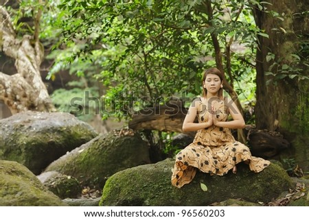 young asian woman meditating in wild forest, thailand - stock photo