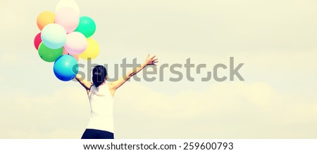 young asian woman mountain peak rock with colored balloons - stock photo