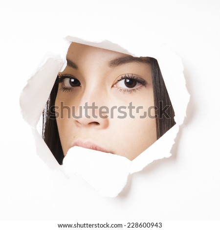 young asian woman peeking through hole torn in paper wall - stock photo