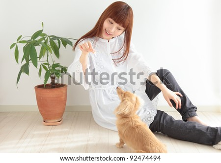 Young Asian woman playing with dachshund - stock photo