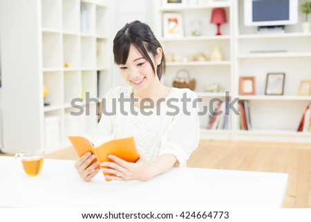 young asian woman reading book in the room - stock photo