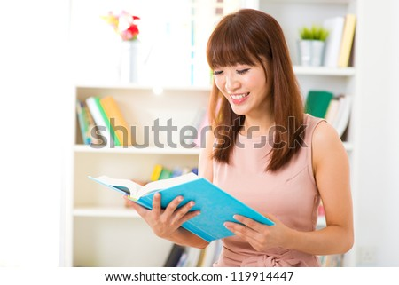 Young Asian woman relaxing at home reading book. - stock photo