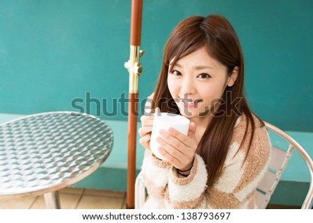 young asian woman relaxing in cafe - stock photo