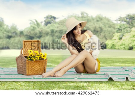 Young asian woman relaxing on the meadow while sitting on mat and holding her dog - stock photo