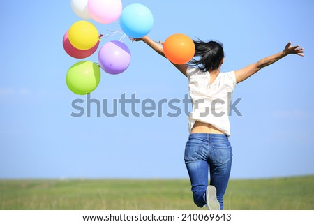 young asian woman running and jumping on green grassland with colored balloons  - stock photo
