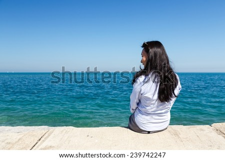 Young Asian woman sits at Lake Michigan in the Hyde Park area of Chicago, IL, USA on a sunny day. - stock photo