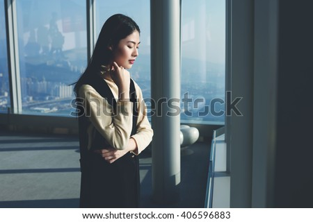 Young Asian woman skilled entrepreneur is looking on a city view from the last floor the tall modern building, while is waiting meeting with international partners during her business trip to New York - stock photo