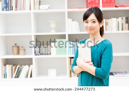young asian woman standing front of book shelf - stock photo