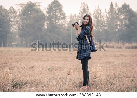 Young Asian woman standing in the field with smiley face. - stock photo