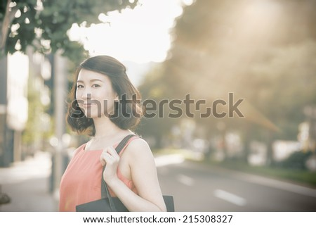 Young Asian woman standing on a city street.(retro effect) - stock photo