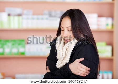 young asian woman suffering from cold standing in a drug store - stock photo