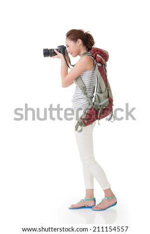 Young asian woman takes images with photo camera. Full length portrait. Isolated on the white background. - stock photo