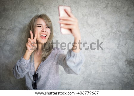 Young asian woman taking a selfie by her smart phone - stock photo