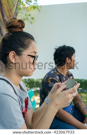 Young Asian woman texting smart phone with friend. - stock photo