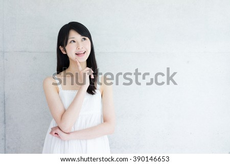 Young Asian woman thinking against concrete wall - stock photo