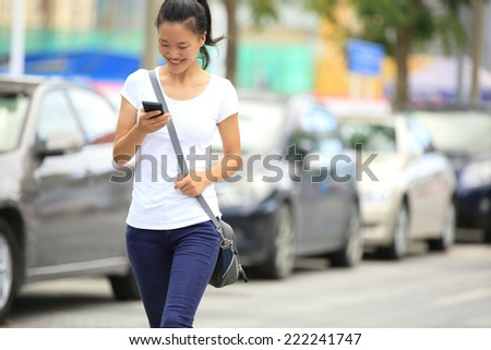young asian woman use her cellphone walking at parking lot  - stock photo