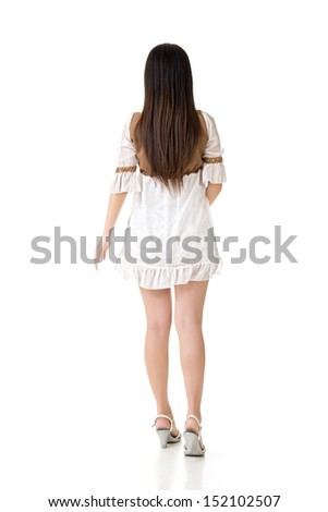 Young asian woman walk in studio. Full length portrait. Rear view. Isolated on the white background. - stock photo