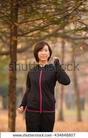 Young Asian woman walking in Autumn Forest. - stock photo