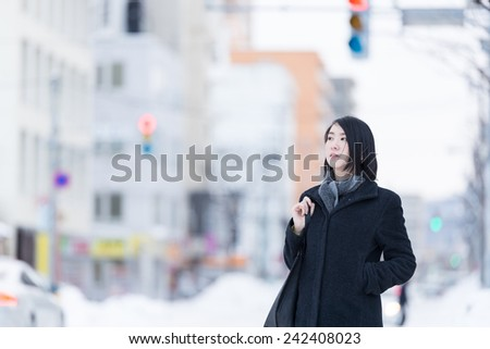 Young Asian woman walking on a winter city. - stock photo