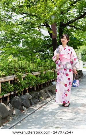 young asian woman wearing kimono walking - stock photo