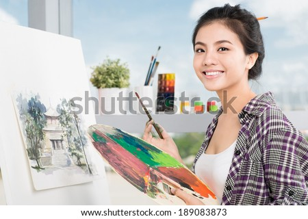 Young Asian woman working on painting in a workshop - stock photo