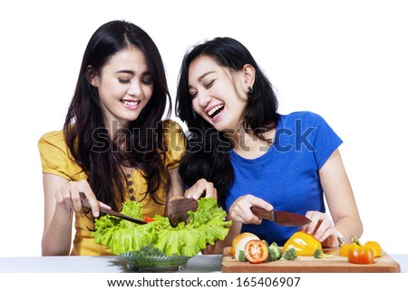 Young asian women prepare salad together - isolated on white background - stock photo