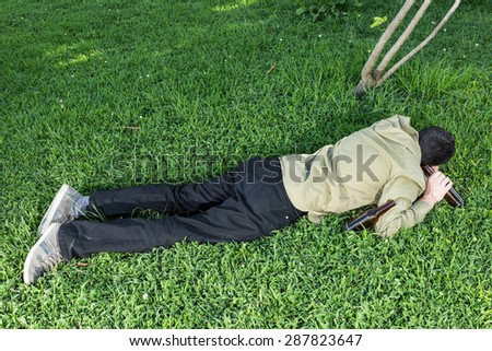 Young asleep or drunk, outdoors on the grass in the park with beer bottles - stock photo
