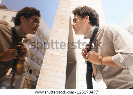 Young aspirational businessman doing up his tie knot using the reflection on a golden mirror modern office building in the city. - stock photo