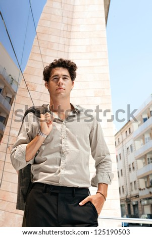Young aspirational businessman holding his suit jacket over his shoulder in a golden mirror modern office building in the city. - stock photo
