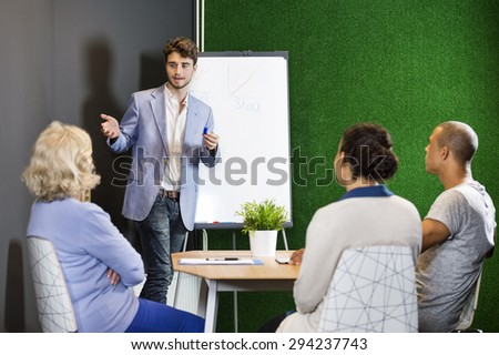 Young associate businessman giving presentation to colleagues at office lobby on casual Friday to a small project team - stock photo