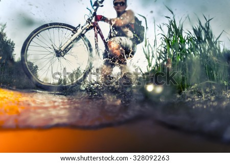 Young athlete crossing the river with bicycle. Focus on the wheel and grass - stock photo