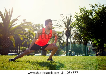 Young athlete doing physical exercises for legs while training outdoors in the park in sunny morning, fit handsome man warming up before begin his run while stretching legs seated on the grass - stock photo