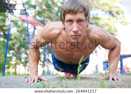 young athlete doing push-ups on the outside - stock photo