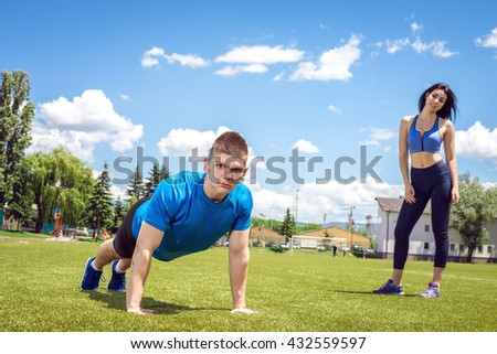 Young athlete doing push ups outdoor on grass football field together with his female partner during hot summer day. Toned image. - stock photo