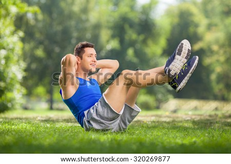 Young athlete doing sit-ups in a grass field on a beautiful sunny day  - stock photo