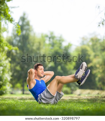 Young athlete doing sit-ups with raised legs in a park on a beautiful summer day shot with tilt and shift lens - stock photo