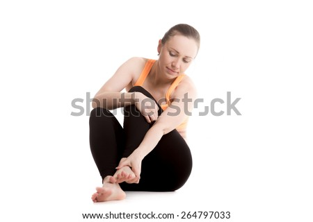 Young athlete girl in sportswear rubbing her foot, injured after sport exercises, feeling pain in ligament, sprained ankle - stock photo