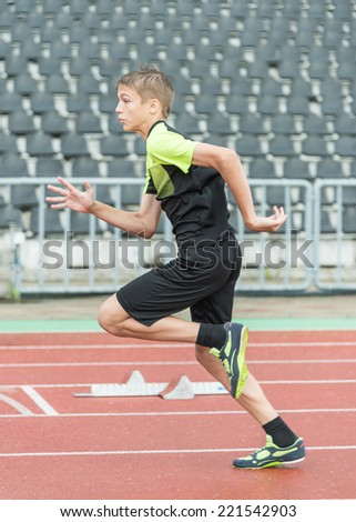 young  athlete is at the start of the treadmill at the stadium  - stock photo
