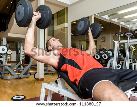Young athlete lifting weight in the gym - stock photo