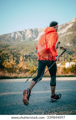 young athlete man running mountain marathon on road, in hands of his walking sticks. background of mountain landscape - stock photo