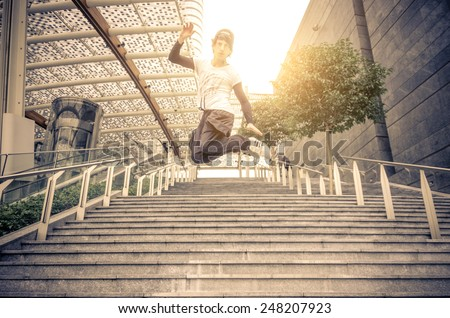 Young athlete performing parkour tricks - Free runner jumping a stairway  - stock photo