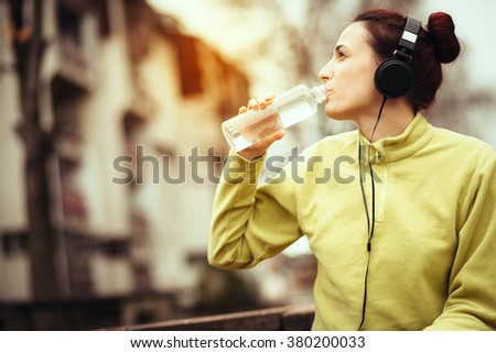young athlete resting and refreshes after running/drinking water - stock photo
