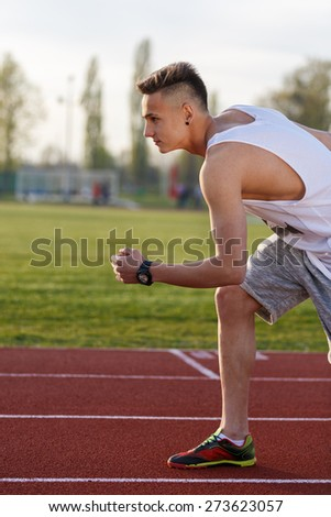 Young athlete running at the running track holding a stopwatch - stock photo